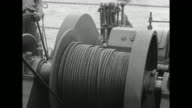 VS sailor unrolls heavy cable from spool with amphibious vehicle in water beyond CU of spool men pulling on cable man's hand on cable control / VS...