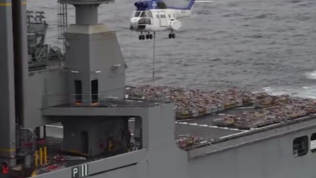 Sailors from weapons department unload ammunition from the USNS Charles Drew to the navy's forwarddeployed aircraft USS Ronald Reagan