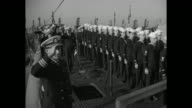 Sailors in formation on deck officers also / sailors and officers turn facing front officers salute / CU sailor with bugle / VS sailor takes American...