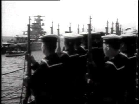 Sailors standing at attention / Rising Sun flag flying / sailors piloting boat