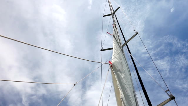 HD: Sails up, sailor is hoisting the mainsail
