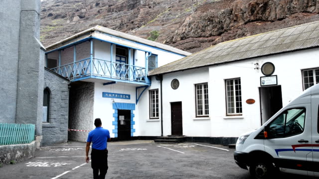 A Saint Helena police officer unlocks the prison gate at Her Majesty Prison and Police Station in Jamestown on Novemeber 1 2017 in the British...