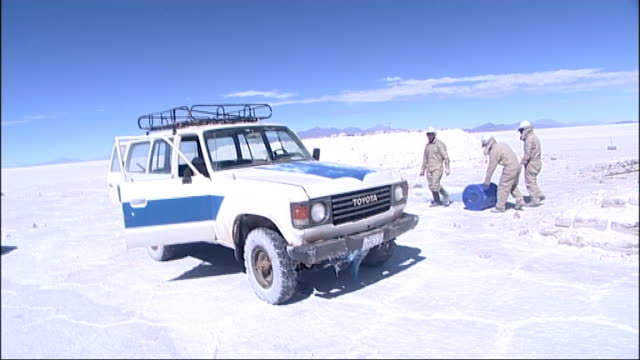 general views / lithium research More shots of Bolivian lithium researchers taking samples of water from collection pools and pouring into blue...