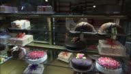 MS Sales clerk arranging cakes in display, North Tehran, Iran