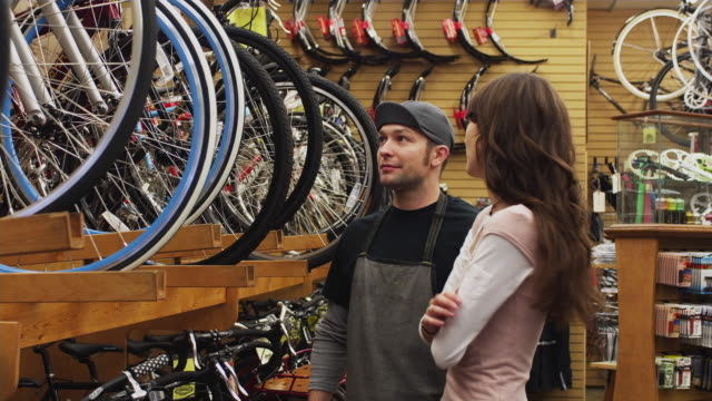 MS Sales clerk assisting young woman in bike shop / Portland, Oregon, USA
