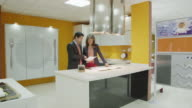 WS TS salesman and female client discussing plans in kitchen showroom; while talking, they walk from one area of the showroom to another, the camera follows them