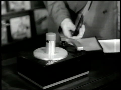 Salesman demonstrating Victor phonograph in store customers CU Victor 45 RPM Record player disks CU Music albums on display WS Customers in record...