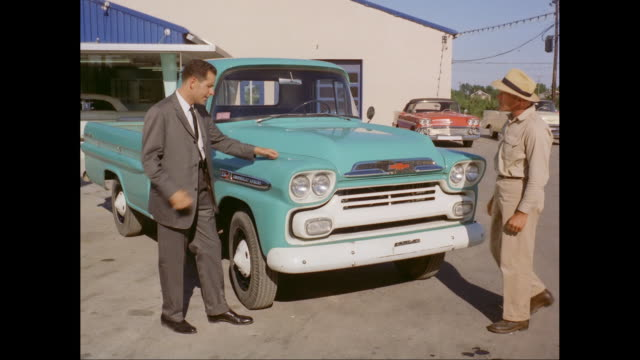 MS Salesman explaining about Chevrolet pick-up truck to customer / United States