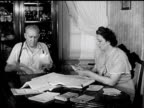 SALESMEN Salesman 'George Meyn' sitting at dining room table w/ wife going over route paperwork accounts