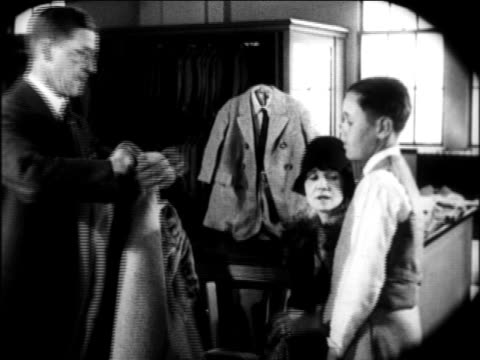 B/W 1924 salesman helping boy try on jacket in menswear store as mother looks on / newsreel