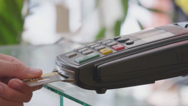 Verkäufer die Einfügung der Kreditkarte in das terminal und Schreibdienste