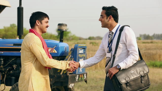 Salesman shaking hand with a farmer, Delhi, India
