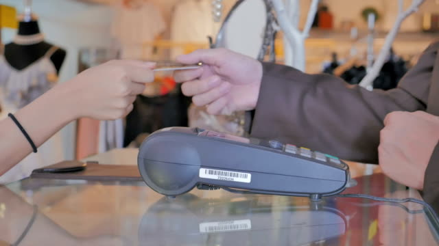 Salesman swiping credit card through credit card reader in boutique