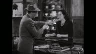 MS Saleswoman showing wrist watch and explaining to customer in shop / United States