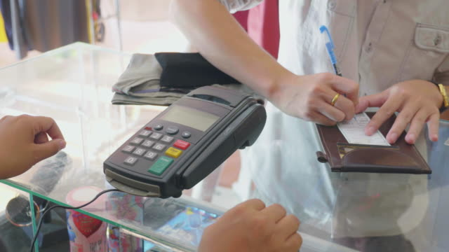 Saleswoman swiping credit card through credit card reader in boutique