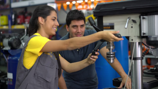 Saleswoman teaching a customer how to use a machine tool both smiling