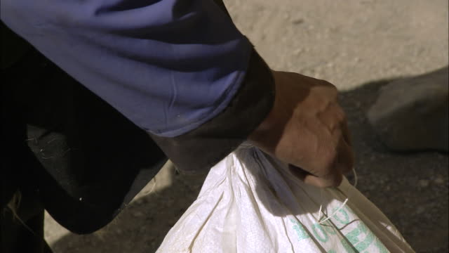 MS Salt trader salt bags putting out of house / Saldang village, High Himalayas, Upper Dolpo near Tibetan border, Nepal