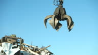 Salvage Yard Grappling Claw Picking Up and Releasing Scrap Metal