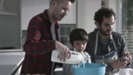 Same sex couple family cooking biscuits