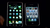 Samsung ordered to pay one billion dollars to Apple ENGLAND London INT Samsung and Apple smartphones placed next to each other and hands touching the...
