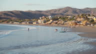 San Juan del Sur beach establishing shot / b-roll. Only few people in a calm orange light sunset of this Latin America town. Fishers arrive to the coast. Local restaurants with palm roof on the background.
