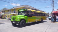 San Juan del Sur Nicaragua. Colorful green bus leaves from Mercado market avenue to Rivas Terminal. Tourists, travelers and locals walking on the street and going by bike.