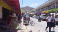 San Juan del Sur Nicaragua. Mercado market avenue. Tourists, travelers and locals walking on the street.