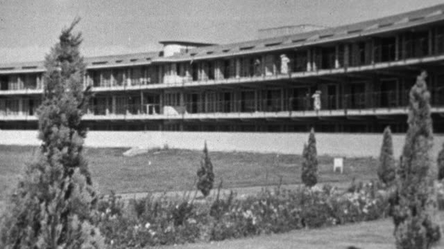 1943 PAN Sanatorium complex and group of nurses walking down sidewalk in front of the facility / United Kingdom