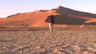 Sand dune, man with tripod walks towards dune, Sossusvlei, Namib-Naukluft, Namibia