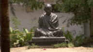 Sandy ground and vegetation surround a statue of Gandhi at the Gandhi Ashram. Available in HD.