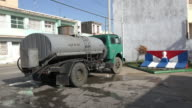 Santa Clara, Cuba: Tank truck transporting water. The vehicle is parked by a Cuban flag and bust of Jose Marti.