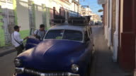 Santa Clara, Cuba: Tourists getting on an old obsolete American car which works as taxi