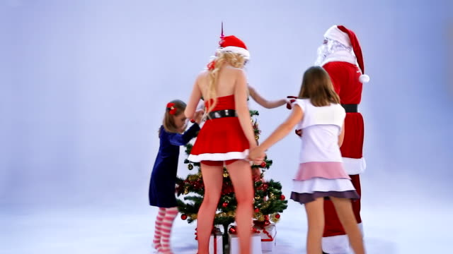 Santa Claus and children dance around a fir tree