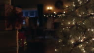 WS Santa Claus entering room to sit near fire and Christmas tree