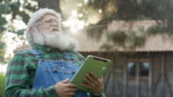 Santa Claus laughing with a digital tablet on his hands.