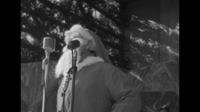 Santa Claus moving around on stage during Christmas celebration held by US Gen James Van Fleet / three shots of Santa Claus standing in front of...
