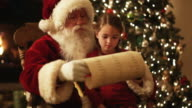 Santa Claus reading a list with a girl on his lap