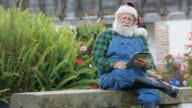 Santa Claus reading childrens mails on his tablet.