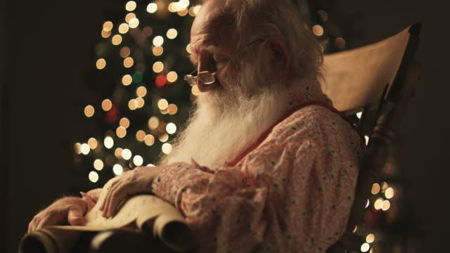 Santa Claus sitting in a rocking chair asleep