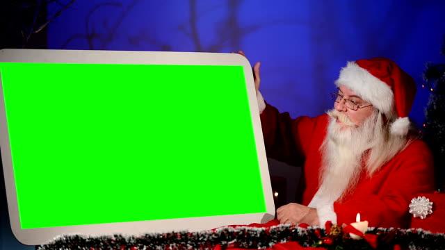 Santa holds empty green sign