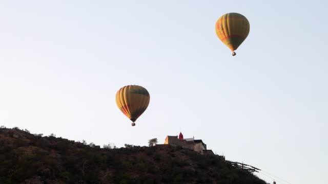 Saraswati Temple perched on top of a hill overlooking Pushkar town being visited by hot air balloons