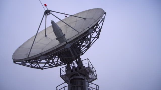 Eine Satellitenschüssel bewegt sich im Zeitraffer und ist Silhouette gegen den Himmel