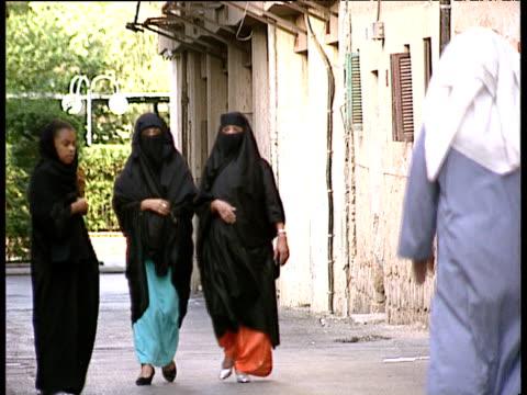 Saudi women in black burkas walking in street shopping at market and with children Saudi Arabia