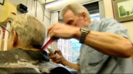 TUC says rise in minimum wage is not enough Mark Payne interview SOT EXT 'Barbers' shopfront window Jim Murdoch cutting man's hair Shaver being used...