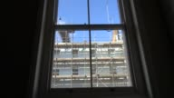 Scaffolding in central London filmed through a sash window from flat on the other side of the street
