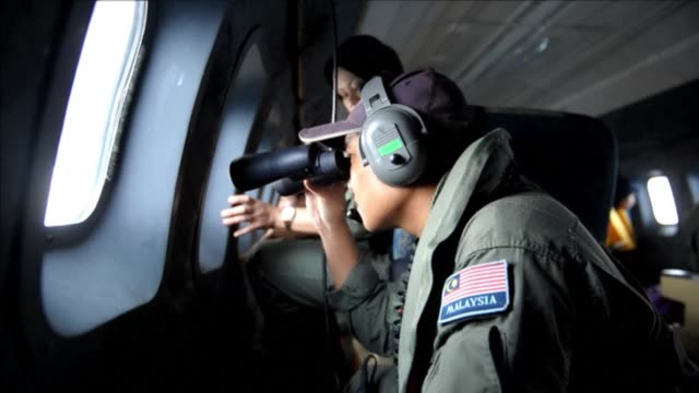Scanning an endless whitespeckled expanse of the blue Andaman Sea the crew of a Malaysian air force plane fight turbulence nausea and mental strain...
