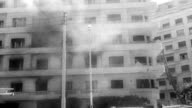 / scenes of violence in Algeria before elections / people outside a residential building looking at smoke billowing from a window / men try to hose...