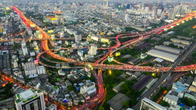 Scenic panoramic view of beautiful highway road traffic lights at night in Bangkok, Thailand.