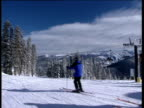 Scenic view of ski slope with snow covered fir trees in background. Skiers ski past camera from right to left ski-lift in distance Winter Park Colorado