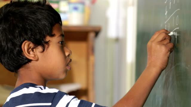 School Boy working out a Math sum